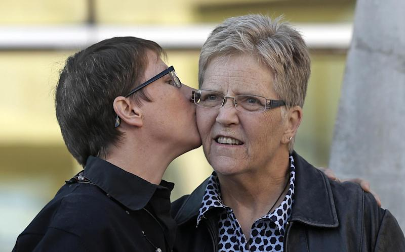 """Kody Partridge, left, kisses Laurie Wood, right, at the Utah Unites for Marriage """"send-off"""" event Monday, April 7, 2014, in Salt Lake City. On Wednesday, April 9, 2014, a three-judge panel in Denver will become the first federal appeals court to hear arguments regarding state same-sex marriage bans since the Supreme Court ruling in June that overturned part of a federal ban on gay marriage. A series of pro-gay marriage rulings in the previous nine months by federal judges has emboldened backers of gay marriage and spurred predictions that it's only a matter of time before gay and lesbian couples will be able to legally marry across the United States. (AP Photo/Rick Bowmer)"""