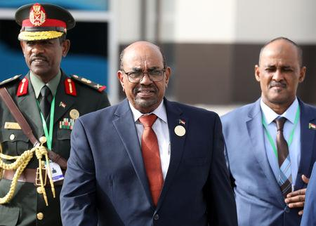 FILE PHOTO - Sudan's President Omar al-Bashir walks with officials as he leaves the African Union summit in Nouakchott