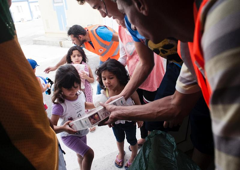A member of the Cyprus Red Cross distributes toys to Syrian and Palestinian refugee children at the Kofinou centre for refugees near the Cypriot coastal city of Larnaca on September 11, 2015 (AFP Photo/Iakovos Hatzistavrou)