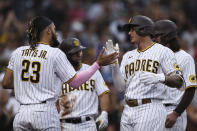 San Diego Padres' Manny Machado, right, is congratulated by Fernando Tatis Jr. (23) after hitting a grand slam against the Atlanta Braves in the fifth inning of a baseball game Saturday, Sept. 25, 2021, in San Diego. (AP Photo/Derrick Tuskan)