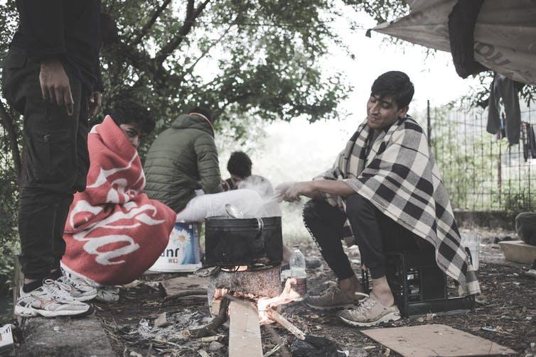Men wrapped in blankets sit around a pot boiling on a fire in a camp on the Bosnian border.