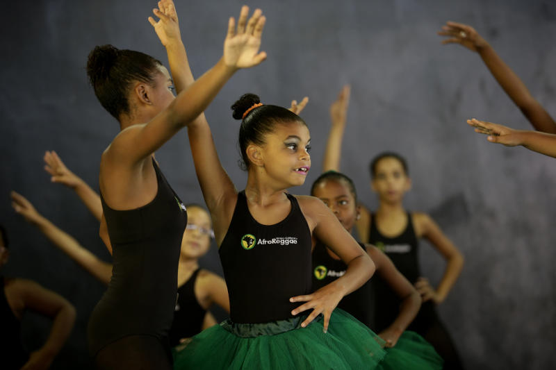 Young dancers from the Afro Reggae center perform before members of London's Royal Opera House in the Vigario Geral slum of Rio de Janeiro, Brazil, Saturday, March 2, 2013. This past week Royal Ballet dancers shared their knowledge and advice with promising artists during an education symposium between the company and the cultural arts center Afro Reggae. (AP Photo/Silvia Izquierdo)