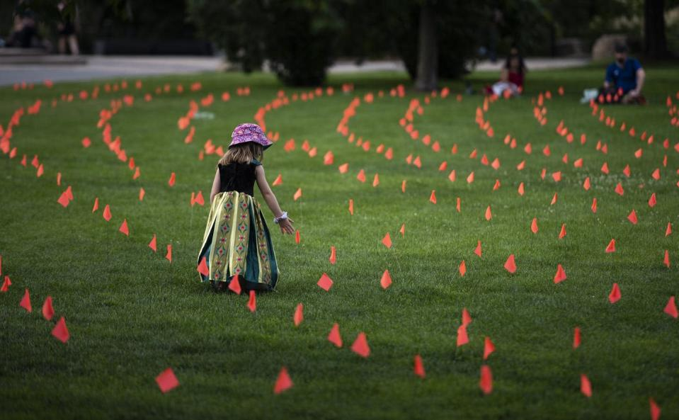 """<span class=""""caption"""">Margot King, age four, touches an orange flag, representing children who died at Indian Residential Schools in Canada, placed in the grass at Major's Hill Park in Ottawa, on July 1, 2021.</span> <span class=""""attribution""""><span class=""""source"""">THE CANADIAN PRESS/Justin Tang</span></span>"""