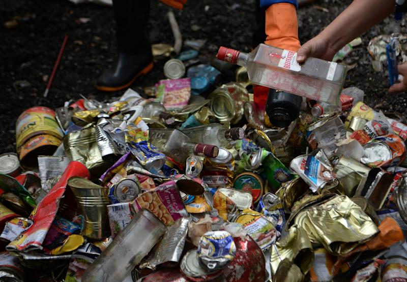 Nepali workers search for recyclable materials froma a pile of waste collected from Mount Everest, in Kathmandu on June 5, 2019. - Aluminium ladders and cans collected from Mount Everest may find a second life as pots and pans, Nepali officials said Wednesday, as some ten tonnes of garbage collected from the world's highest mountain was handed over for recycling. The 14-strong team sent by the government spent about six weeks scouring for litter from base camp to Camp 4 -- nearly 8,000 metres (26,300 feet) up -- scraping together empty cans, bottles, plastic and discarded climbing gear. (Photo by PRAKASH MATHEMA / AFP) (Photo credit should read PRAKASH MATHEMA/AFP/Getty Images)
