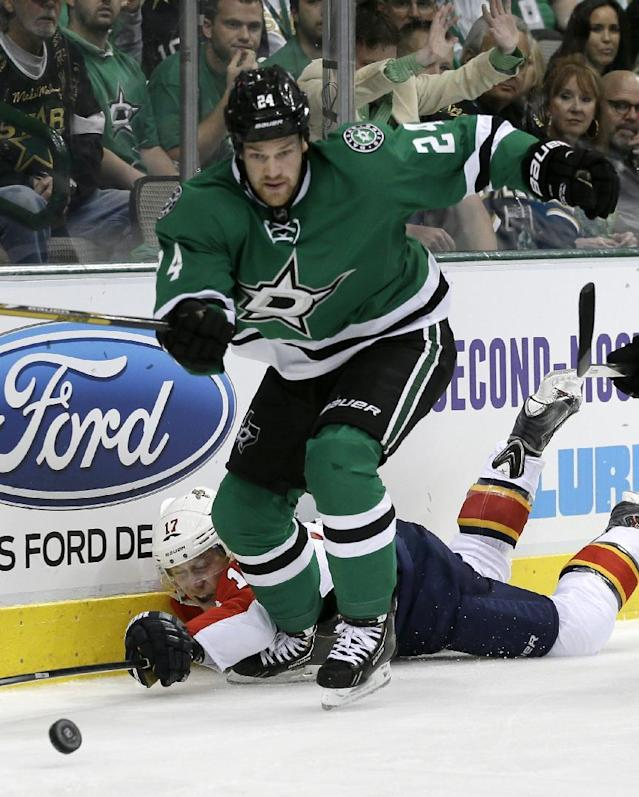 Dallas Stars defenseman Jordie Benn (24) chases down a loose puck in front of Florida Panthers center Jesse Winchester in the second period of an NHL hockey game, Thursday, Oct. 3, 2013, in Dallas. (AP Photo/Tony Gutierrez)
