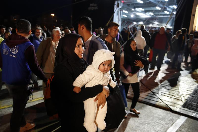 An Afghan mother holds her child upon their arrival from Lesbos island to the port of Piraeus, near Athens, Monday Oct. 7, 2019. In the last 24 hours 668 refugees and migrants have been transferred to mainland Greece from five Greek islands as authorities have accelerated efforts to ease over crowding in the camps. (AP Photo/Thanassis Stavrakis)