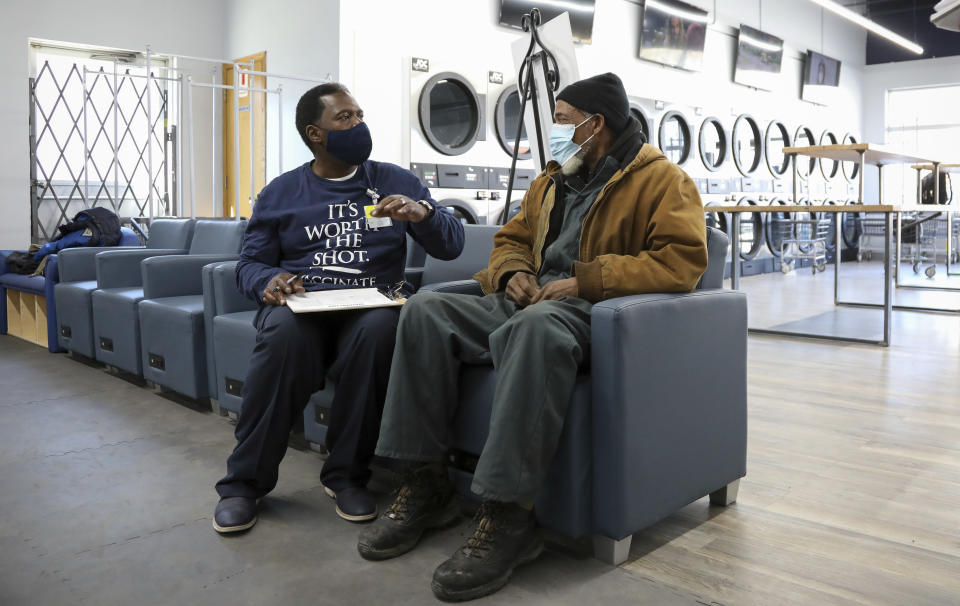 Herman Simmons, left, makes a vaccination appointment for Theopulis Polk, right, at a Chicago laundromat on Saturday, March 6, 2021. Simmons is a community outreach worker enlisted by Saint Anthony Hospital. ''I see myself as my brother's keeper. I don't try to force them. I'm persistent,'' he said. In a race to boost vaccination rates as COVID-19 variants spread, U.S. communities are working to overcome mistrust and improve access among people of color. (AP Photo/Teresa Crawford)