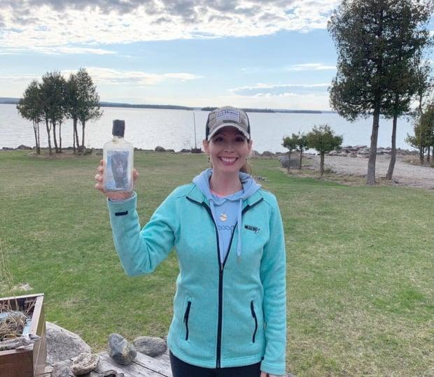 Shandelle Carrigan holds up the bottle she found on Barrie Island in mid-April. The message inside eventually led to finding the Walli family, who threw it into Lake Huron more than four years ago. (Shandelle Carrigan/Facebook - image credit)