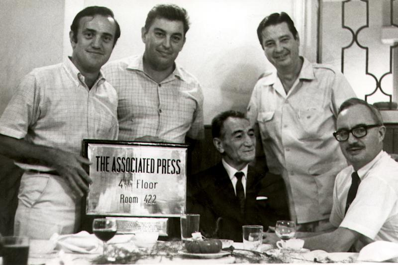 In this circa 1968-69 photo, AP Saigon staffers, correspondent Peter Arnett, left, photo chief Horst Faas, second left, and Chief of Bureau George McArthur, second right, and Edwin Q. White, right, pose for a photo with: Jean Ottavi, owner of the Royal Hotel in Saigon. White, a Saigon bureau chief for The Associated Press during the U.S. buildup in the Vietnam War, died Thursday, Nov. 1, 2012 in Honolulu at age 90. (AP Photo)