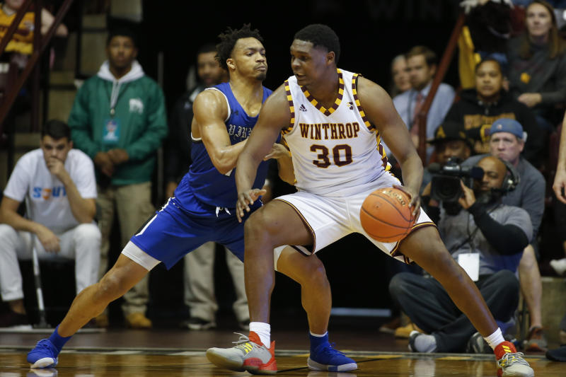 Winthrop forward D.J. Burns, right, drives into Hampton forward Benjamin Stanley in the second half of an NCAA college basketball game for the Big South tournament championship in Rock Hill, S.C., Sunday, March 8, 2020. (AP Photo/Nell Redmond)