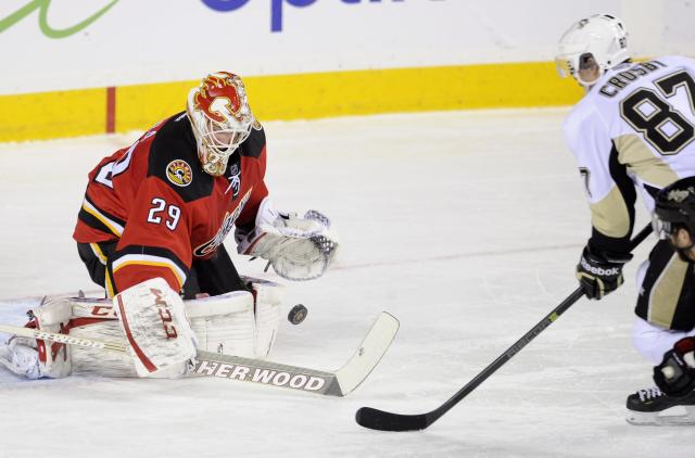 Pittsburgh Penguins' Sydney Crosby, right, has a shot stopped by Calgary Flames' goalie Reto Berra, from Switzerland, during first-period NHL hockey game action in Calgary, Alberta, Saturday, Jan. 11, 2014. (AP Photo/The Canadian Press, Larry MacDougal)