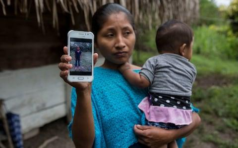 Claudia Maquin, 27, shows a photo of her daughter, Jakelin, at her home in Raxruha, Guatemala  - Credit: Oliver de Ros/AP