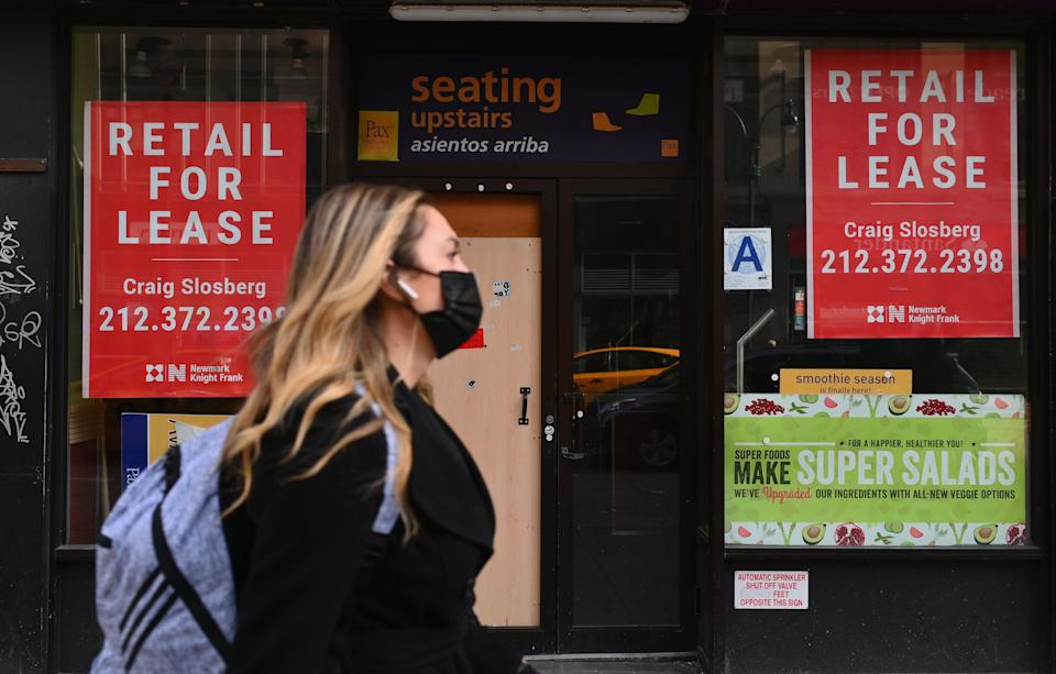 A woman walks past a closed retail store for lease in midtown Manhattan.