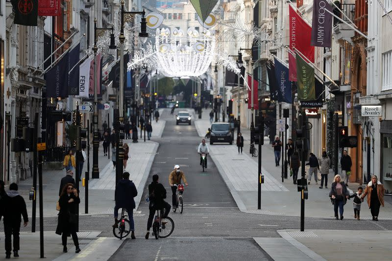 FILE PHOTO: Pedestrians and cyclists move through New Bond Street amid the coronavirus disease (COVID-19) outbreak in London