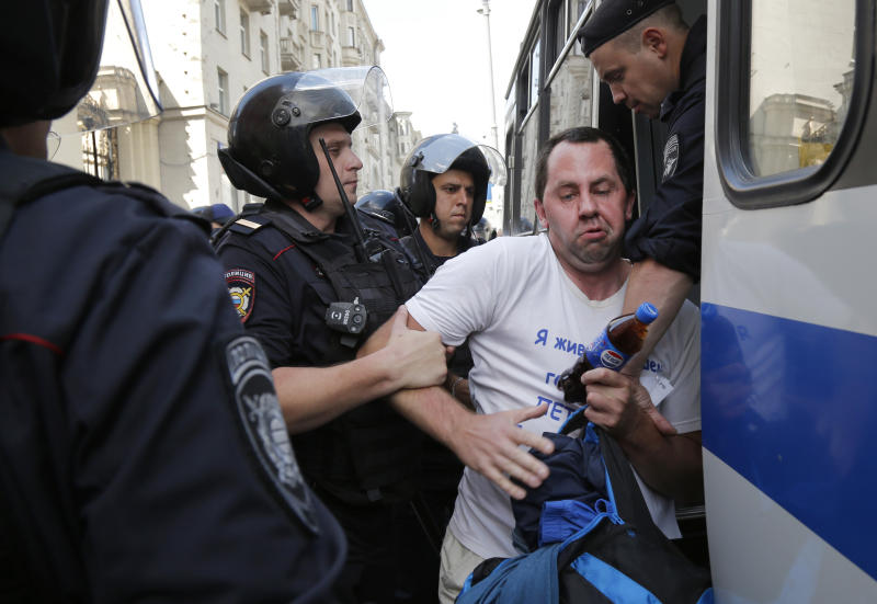 Police officers detain a man prior to an unsanctioned rally in the center of Moscow, Russia, Saturday, July 27, 2019. OVD-Info, an organization that monitors political arrests, said about 50 people had been detained by 1:30 p.m. Saturday (1030 GMT), a half-hour before the protest against the exclusion of opposition figures from the ballot for city council elections was to start. (AP Photo/Alexander Zemlianichenko)