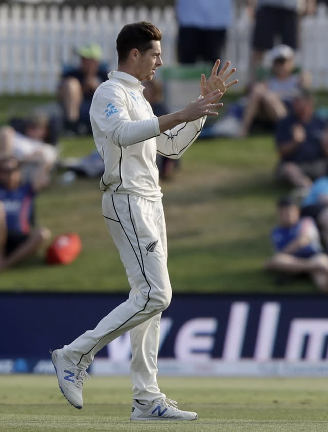 Mitch Santner celebrates after taking the wicket of Rory Burns (Mark Baker/AP)
