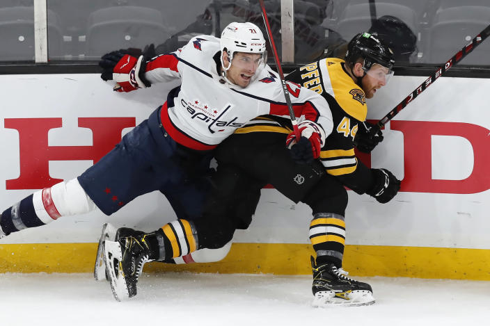Washington Capitals' Garnet Hathaway (21) and Boston Bruins' Steve Kampfer (44) battle along the boards during the first period of an NHL hockey game, Sunday, April 18, 2021, in Boston. (AP Photo/Michael Dwyer)