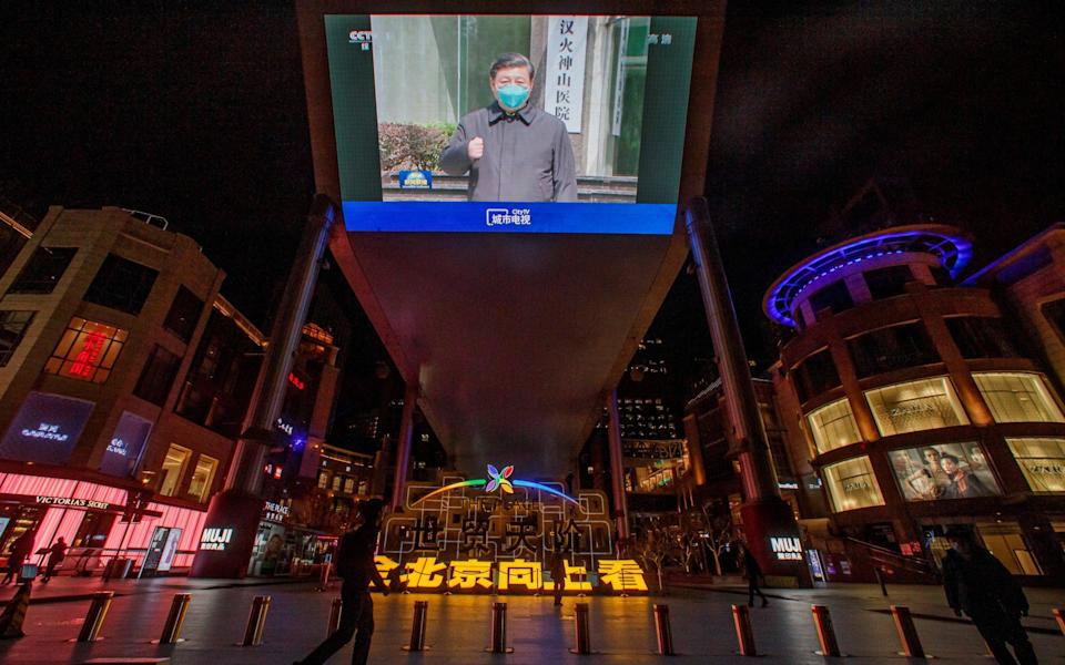 A screen shows a CCTV state media broadcast of Chinese President Xi Jinping's visit to Wuhan, at a shopping centre in Beijing - THOMAS PETER/REUTERS