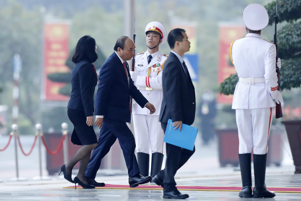 Vietnam Prime Minister Nguyen Xuan Phuc, second left, arrives at the national convention center to attend the 13th Communist Party Congress in Hanoi, Vietnam Tuesday, Jan. 26, 2021. Vietnam's ruling Communist Party has begun a crucial weeklong meeting in the capital Hanoi to set the nation's path for the next five years and appoint the country's top leaders. (AP Photo/Minh Hoang)