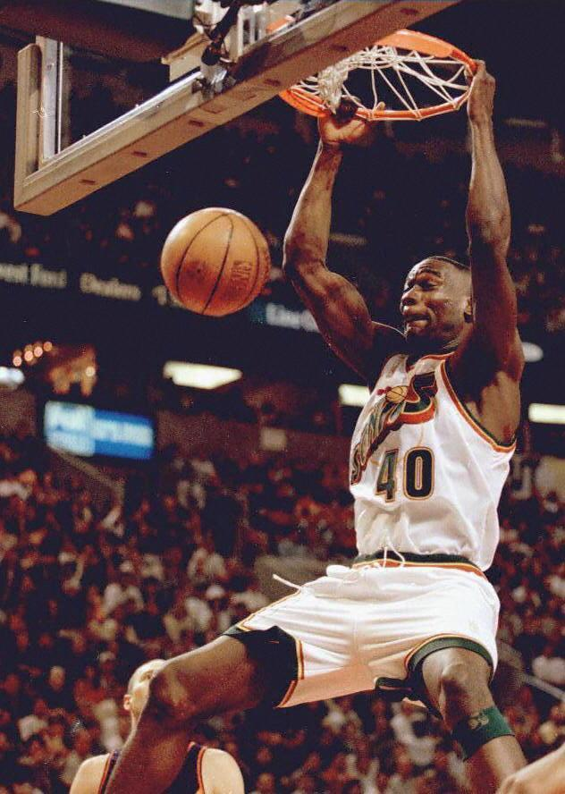 Seattle Sonics player Shawn Kemp slam dunks the ball against the Phoenix Suns in May 1997. / Credit: DAN LEVINE/AFP via Getty