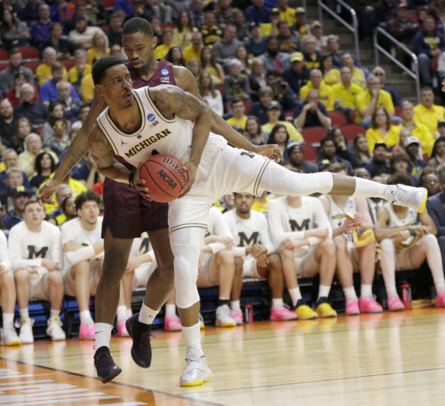 Michigan's Charles Matthews, front. keeps the ball in play in front of Montana's Sayeed Pridgett during the first half of a first round men's college basketball game in the NCAA Tournament in Des Moines, Iowa, Thursday, March 21, 2019. (AP Photo/Nati Harnik)