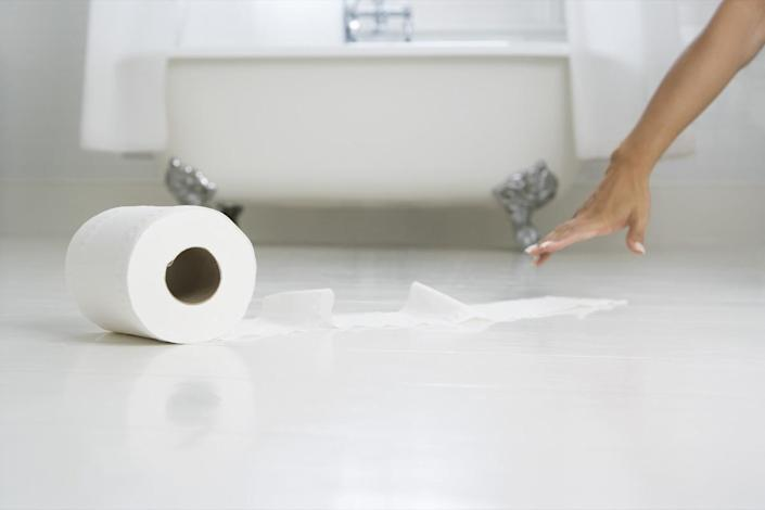 woman's hand reaching tissue paper in bathroom