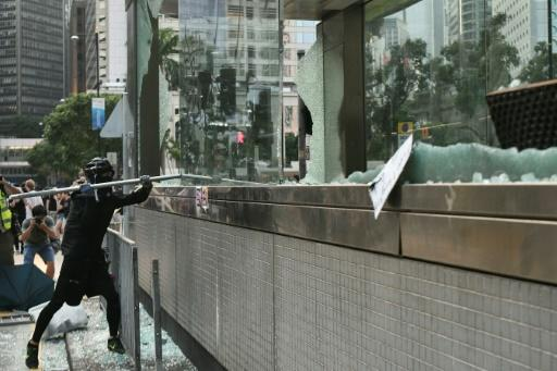 A hardcore Hong Kong protester uses a metal pole to smash glass outside an exit of the Central MTR underground metro station
