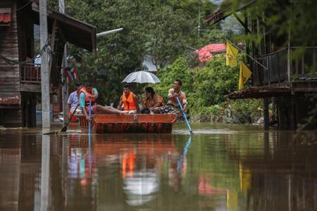 People paddle as they travel along a flooded street by boat at Kabin Buri district in Prachin Buri September 29, 2013. REUTERS/Athit Perawongmetha
