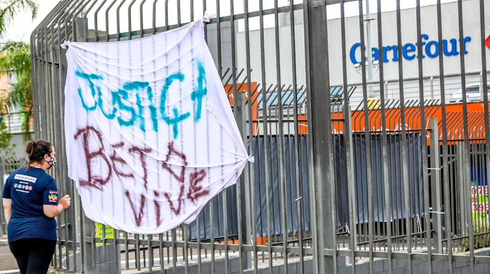 "A banner reading ""Justice, Beto lives"" hangs on a fence in front of the Carrefour supermarket in Porto Alegre, Rio Grande do Sul, Brazil on November 20, 2020. - The death on Thursday night of a black man after being beaten by white security agents in a supermarket belonging to the Carrefour group in Porto Alegre unleashed a wave of indignation in Brazil, which this Friday commemorates Black Consciousness Day. (Photo by SILVIO AVILA / AFP) (Photo by SILVIO AVILA/AFP via Getty Images)"