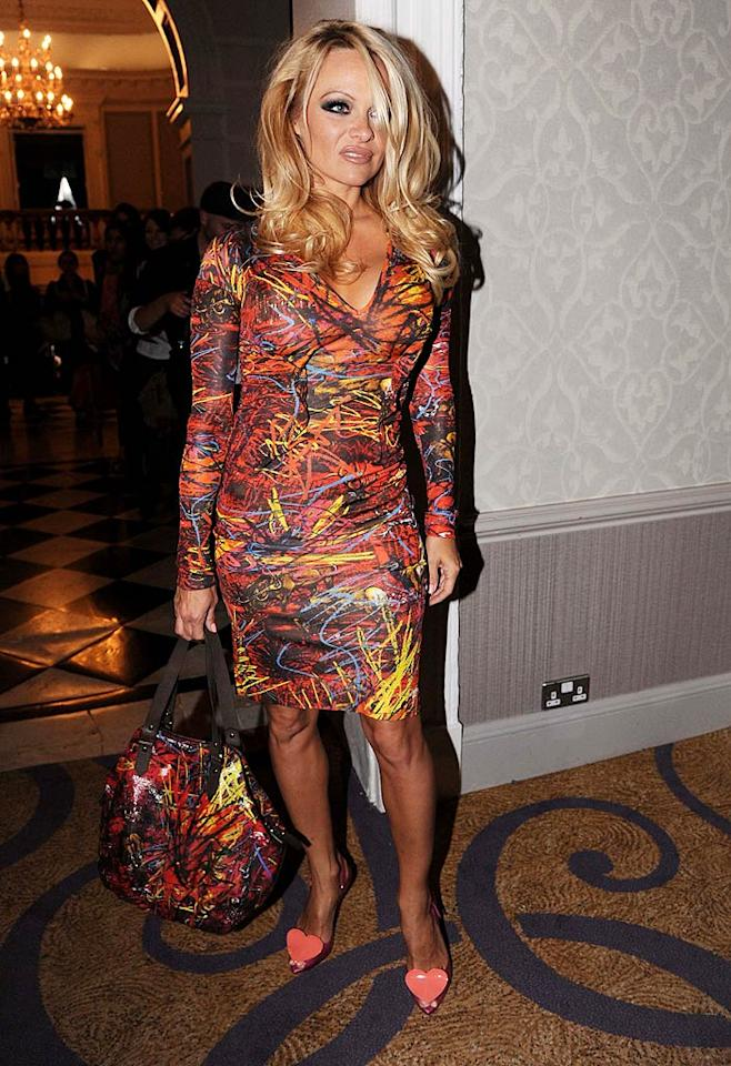 """Pamela Anderson donned a Vivienne Westwood scribble-print dress to the designer's Red Label show on Sunday at London Fashion Week. Even the former """"Baywatch"""" babe seemed a little unsure of the busy frock, which she paired with a matching handbag and heart-adorned shoes. <a href=""""http://www.splashnewsonline.com/"""" target=""""new"""">Splash News</a> - September 19, 2010"""