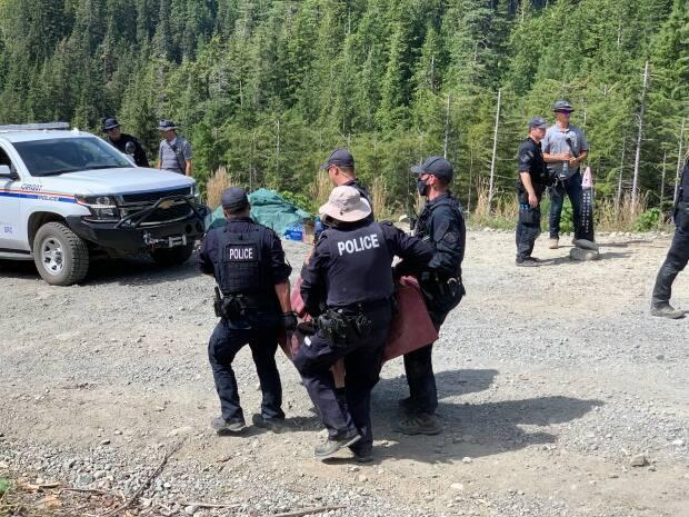 RCMP officers carry a person who was removed from a blockade and arrested at a protest near the Fairy Creek watershed on southern Vancouver Island in August.  (Kathryn Marlow/CBC News - image credit)