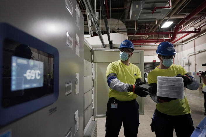 Workers handle boxes containing the Pfizer-BioNTech COVID-19 vaccine as they are prepared to be shipped at the Pfizer Global Supply Kalamazoo manufacturing plant in Portage, Mich., Sunday, Dec. 13, 2020. (AP Photo/Morry Gash, Pool)