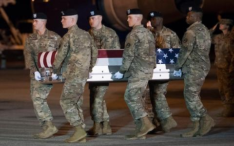 An Army carry team moves a transfer case containing the remains of Sgt. 1st Class Elis Barreto Ortiz - Credit: Cliff Owen/AP