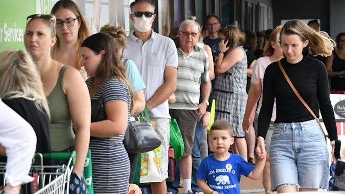 People queue for groceries outside a supermarket in Brisbane on Friday