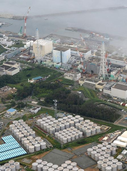 This Aug. 20, 2013 aerial photo shows the Fukushima Dai-ichi nuclear plant at Okuma in Fukushima prefecture, northern Japan. The Japanese nuclear watchdog proposed Wednesday to define a fresh leakage of highly radioactive leak from one of the hundreds of storage tanks at Japan's crippled atomic power plant this week, its worst leak yet from such a vessel. The operator of the Fukushima Dai-ichi plant said Tuesday said about 300 tons (300,000 liters, 80,000 gallons) of contaminated water have leaked from a steel storage tank at the wrecked Fukushima Dai-ichi plant. TEPCO hasn't figured out how or where the water leaked, but suspects it did so through a seam on the tank or a valve connected to a gutter around the tank. (AP Photo/Kyodo News) JAPAN OUT, MANDATORY CREDIT