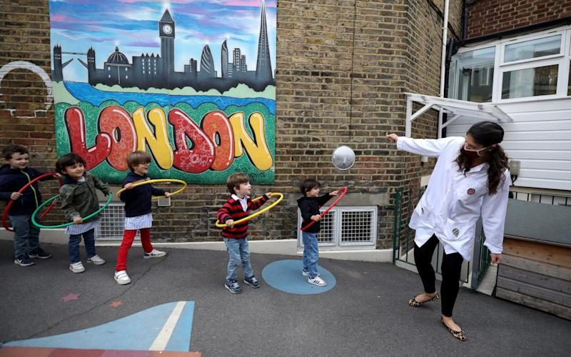 Children use hoops for social distancing at L'Ecole des Petits, an independent French bilingual school in Fulham. - KEVIN COOMBS/REUTERS