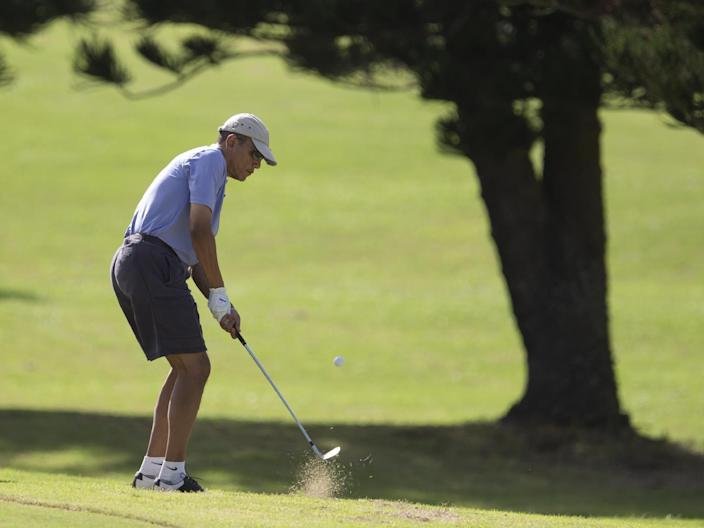 U.S. President Barack Obama hits his approach shot to the 18th green as he golfs at Mid-Pacific County Club in Kailua, Hawaii, Monday, Dec. 23, 2013. The first family is in Hawaii for their annual holiday vacation. (AP Photo/Carolyn Kaster)