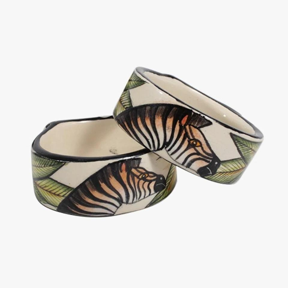 """andBeyond has made a name operating socially responsible safaris across Africa, South America, and Asia. Their commitment to their local community carries over to their shop, which features wares handmade by artisans in those areas where andBeyonds can be found. These zebra napkin rings by Ardmore are made by craftspeople in the Midlands of KwaZulu-Natal, South Africa. $258, ARDMORE. <a href=""""https://www.ardmore-design.com/collections/ceramics/products/zebra-napkin-ring?variant=32137622880369"""" rel=""""nofollow noopener"""" target=""""_blank"""" data-ylk=""""slk:Get it now!"""" class=""""link rapid-noclick-resp"""">Get it now!</a>"""