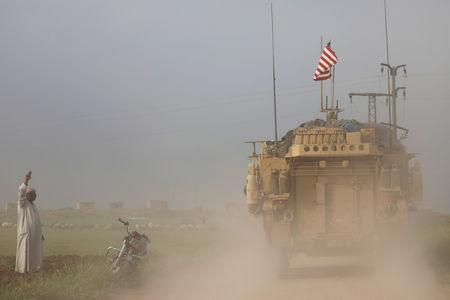 A man gestures at U.S military vehicles driving in the town of Darbasiya next to the Turkish border