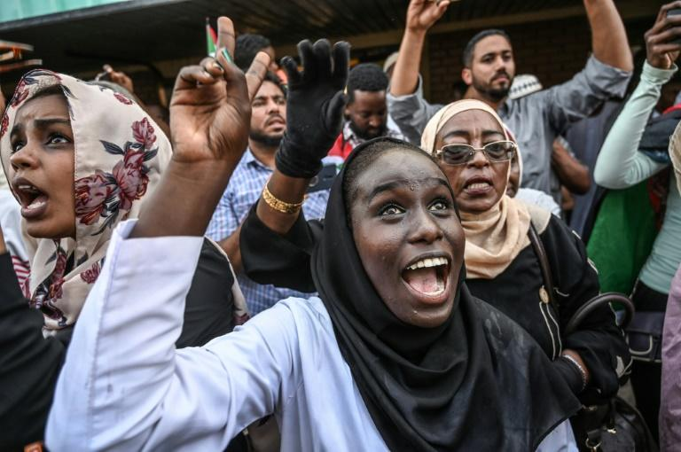 Sudanese protesters cheer fellow demonstrators arriving in Khartoum by train