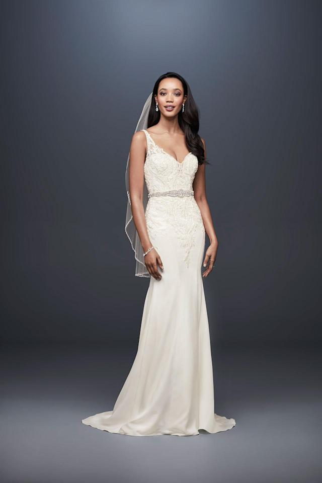 <p>A lacy cream dress and veil. (Photo: Courtesy of David's Bridal) </p>