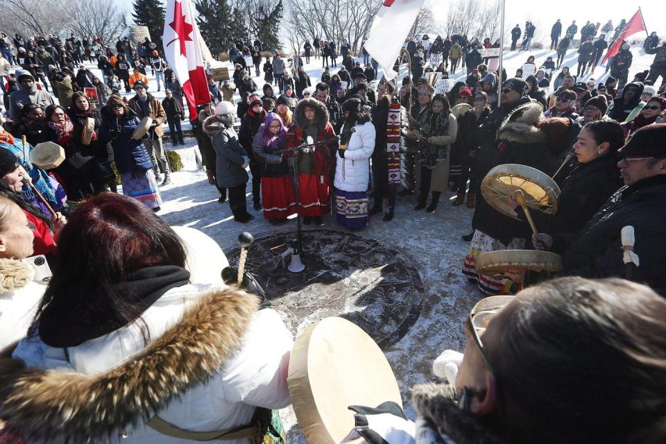 Indigenous protesters, some wearing ribbon skits, some holding drums stand in a circle in the winter.
