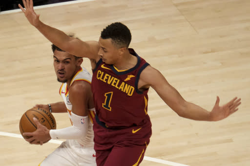 Atlanta Hawks guard Trae Young (11) gets pressured by Cleveland Cavaliers guard Dante Exum (1) during the first half of an NBA basketball game on Saturday, Jan. 2, 2021 in Atlanta. (AP Photo/Ben Gray)