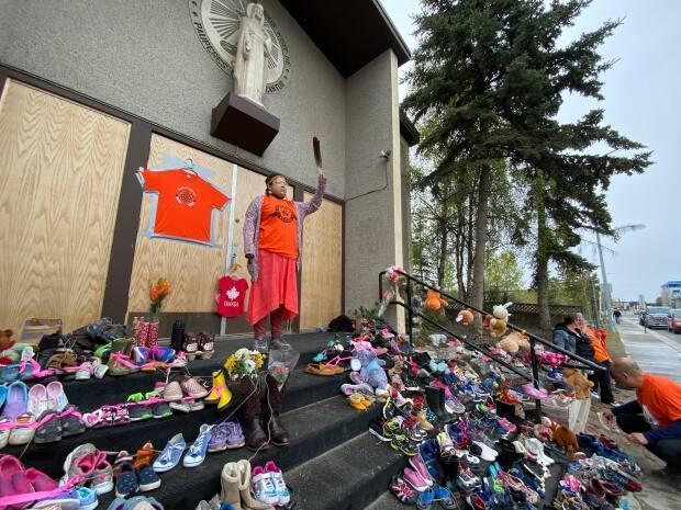 A vigil outside the Sacred Heart Cathedral in Whitehorse on Monday. Hundreds of pairs of childrens' shoes have been left in front of the Catholic church.