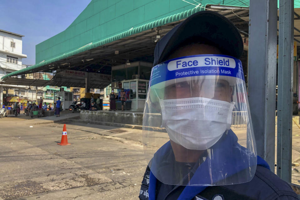 FILE - In this Dec. 20, 2020, file photo, a guard with a face-shield stands near a shrimp market in Samut Sakhon, south of Bangkok. Thailand, which has kept the coronavirus largely in check for most of the year, is facing a challenge from a large outbreak of the virus among migrant workers in the province close to Bangkok.(AP Photo/ Jerry Harmer, File)