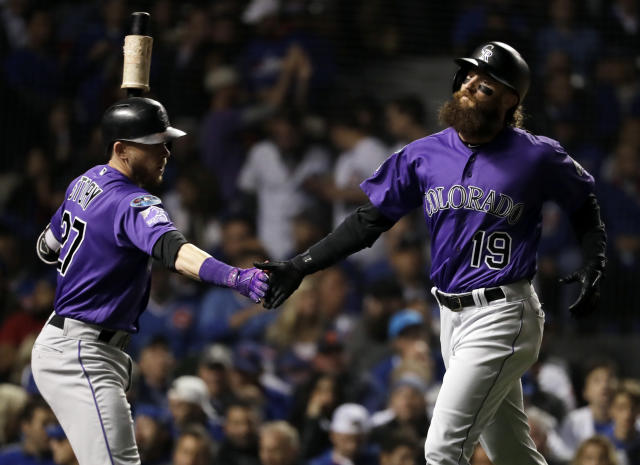 Colorado Rockies' Charlie Blackmon, right, celebrates with Trevor Story after scoring on a sacrifice fly by Nolan Arenado during the first inning of the National League wild-card playoff baseball game against the Chicago Cubs, Tuesday, Oct. 2, 2018, in Chicago. (AP Photo/Nam Y. Huh)