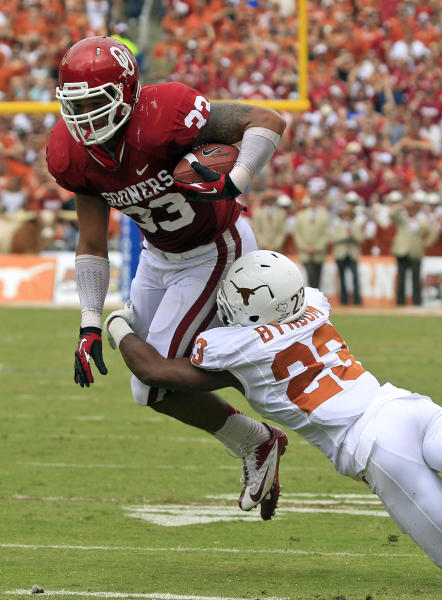 Oklahoma fullback Trey Millard (33) is grabbed by Texas cornerback Carrington Byndom (23) during the first half of an NCAA college football game at the Cotton Bowl Saturday, Oct. 13, 2012, in Dallas. (AP Photo/LM Otero)