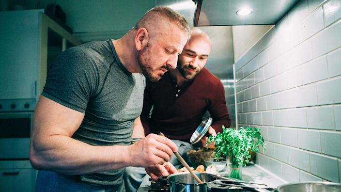 homosexual couple stands together in the kitchen at the stove and tasting the meal.