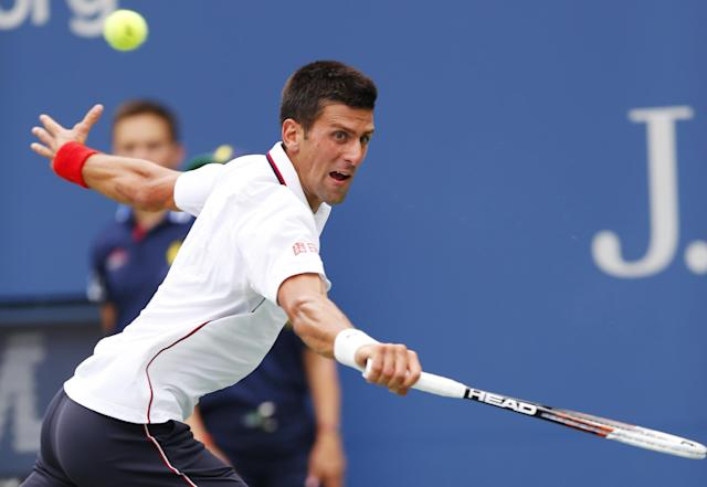 Novak Djokovic, of Serbia, returns a shot against Sam Querrey, of the United States, during the third round of the 2014 U.S. Open tennis tournament, Saturday, Aug. 30, 2014, in New York. (AP Photo/Matt Rourke)