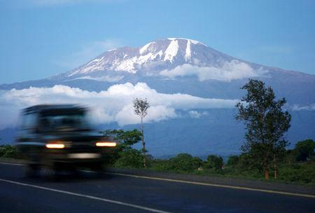 FILE PHOTO: A vehicle drives past Mount Kilimanjaro in Tanzania's Hie district December 10, 2009. REUTERS/Katrina Manson